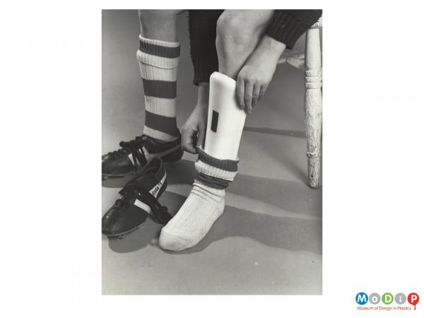 Scanned image showing shin pads in use.