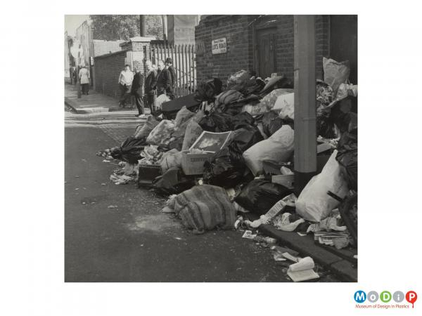 Scanned image showing a street scene depicting piles of filled rubbish bags.