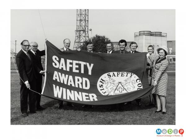 Scanned image showing the presentation of a safety award flag.