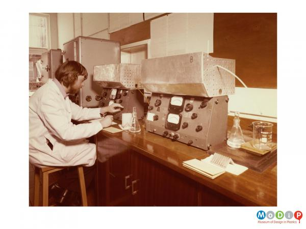 Scanned image showing a man using laboratory equipment.