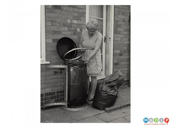 Scanned image showing a woman wearing an apron changing a bin bag in an external bin.