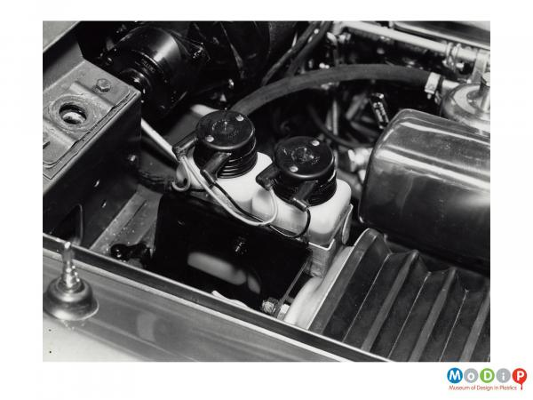 Scanned image showing two fluid containers in the engine bay of a car.
