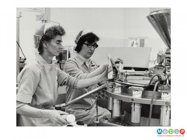 Scanned image showing two women removing filled tubes from a sealing machine.