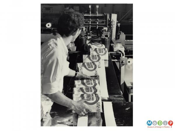 Scanned image showing packets of kitchen towels coming off a production line.