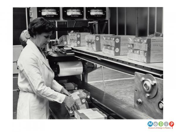 Scanned image showing a woman packing boxes in a shrink wrapping machine.