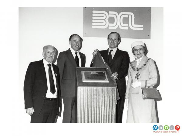Scanned image showing three men and woman at the opening of a new factory.