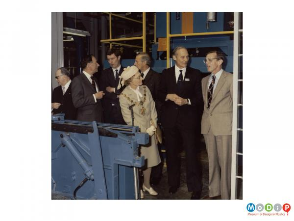 Scanned image showing a group of people at the opening of a new factory.