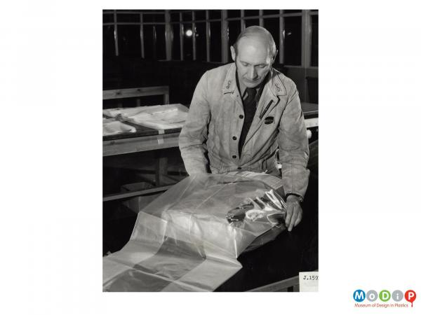 Scanned image showing a man putting a parcel into a polythene sack.