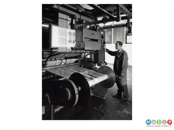 Scanned image showing a man at a printing machine.