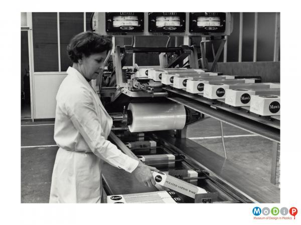 Scanned image showing a woman putting boxes into a wrapping machine.