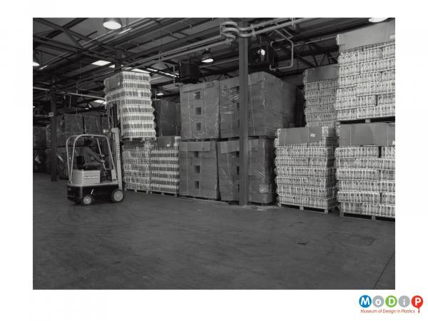 Scanned image showing a fork lift truck moving loaded pallets.