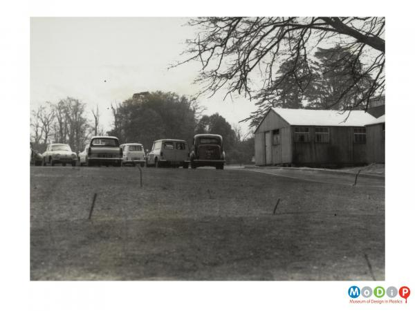 Scanned image showing cars parked by an outbuilding.
