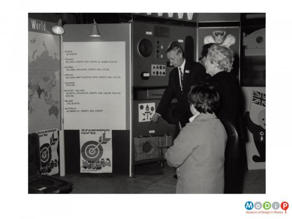Scanned image showing visitors to the factory looking at display boards showing information about the BXL company and its products.