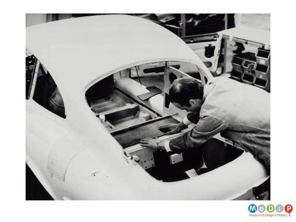 Scanned image showing  male worker fitting a Plastazote panel into the back of an E-type jag.