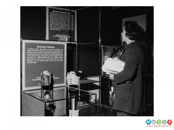 Scanned image showing a woman looking at a display stand.