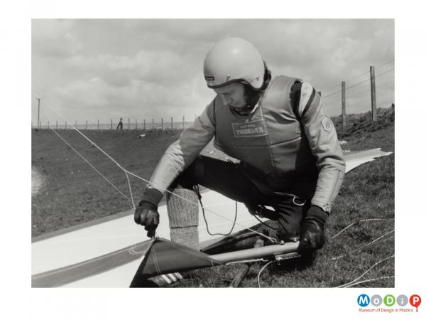 Scanned image showing a man alongside a hang-glider.