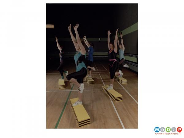 Scanned image showing a group of women using blocks of material for step- aerobics.