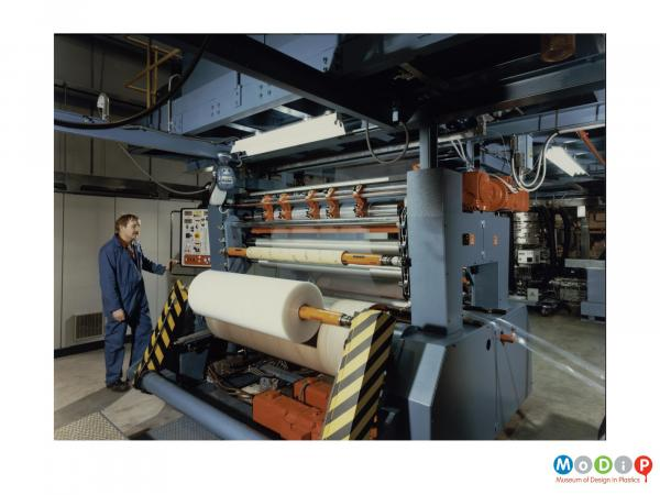 Scanned image showing a machine with a roll of sheet material at the front.