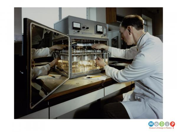 Scanned image showing a man in a white coat using a scientific device.