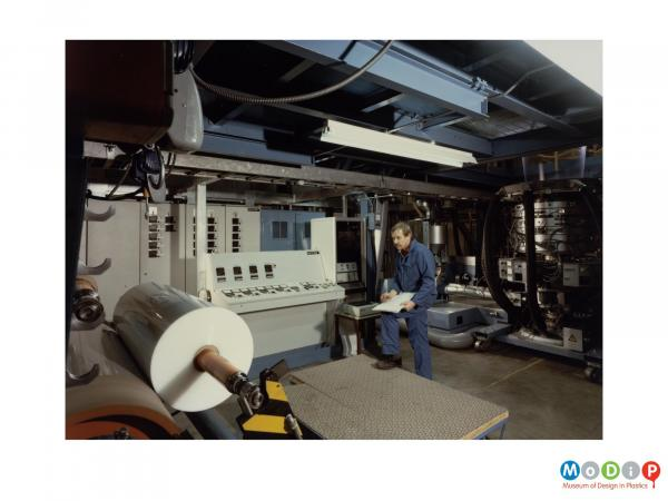 Scanned image showing a man in blue overalls taking notes by an extruding machine.