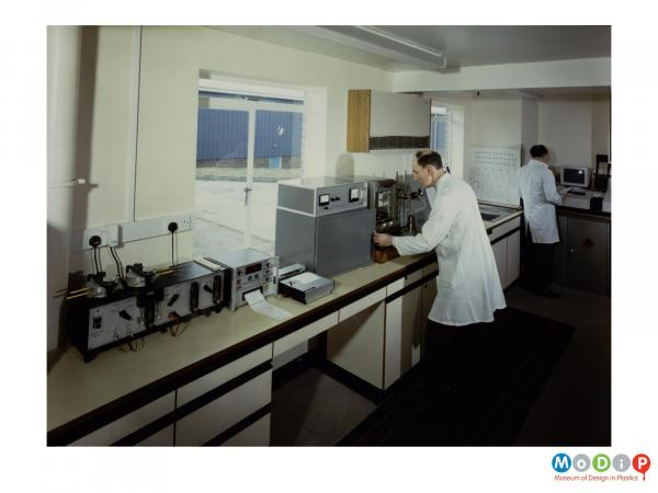 Scanned image showing two men wearing white coats in a laboratory.