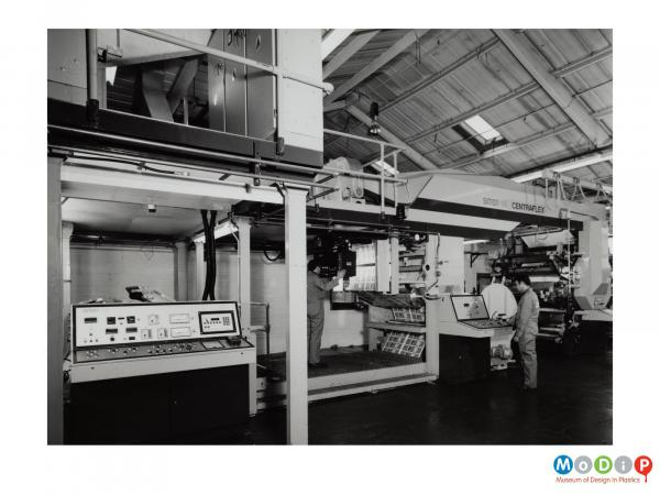 Scanned image showing two male employees and a large piece of machinery.