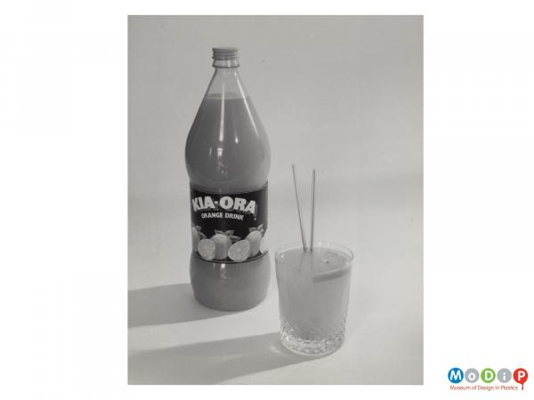 Scanned image showing a bottle of Kia-Ora orange drink along side a tumbler with 2 straws.