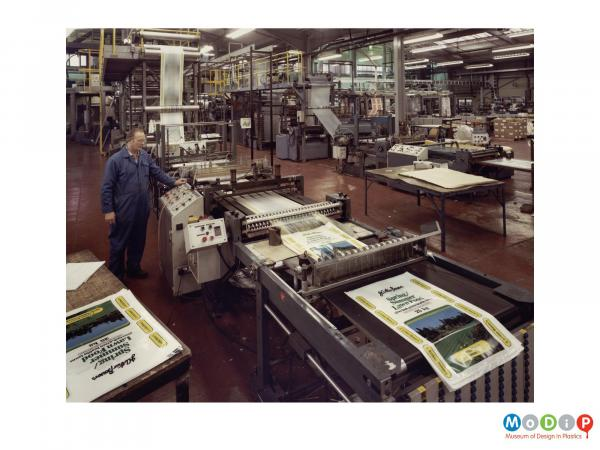 Scanned image showing a male worker operating a machine cutting bags.