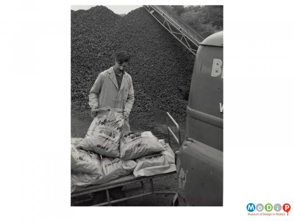 Scanned image showing sacks of coal being loaded into a van.