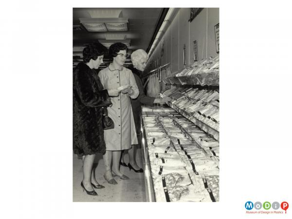 Scanned image showing shoppers in a supermarket.
