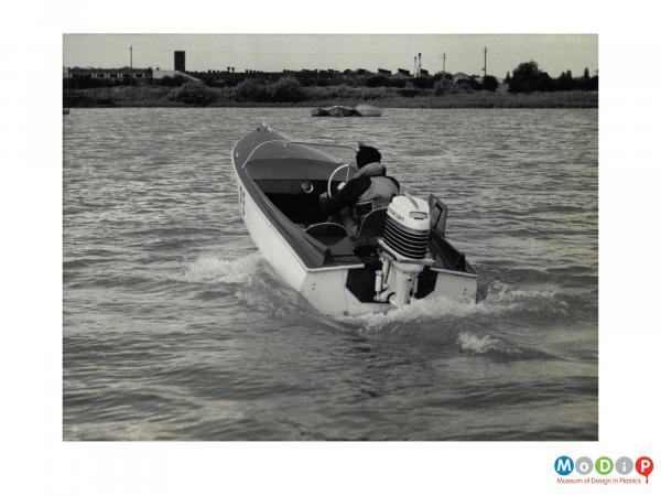 Scanned image showing a small motor boat on the water.