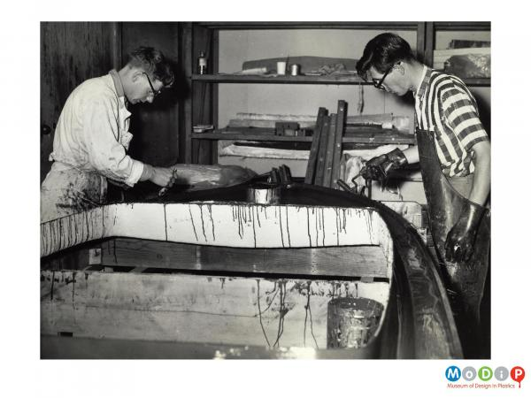 Scanned image showing a small boat being built.