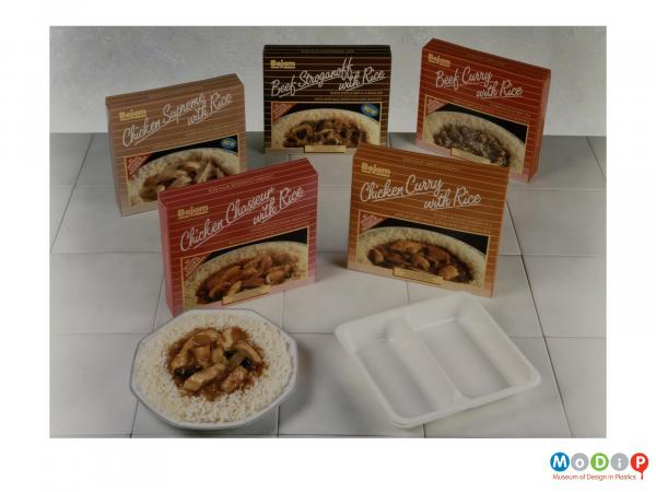Scanned image showing 5 boxed ready meals behind a ready meal tray and a meal arranged on a plate.