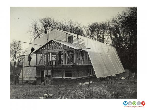 Scanned image showing a house being protected by sheet plastic during building.