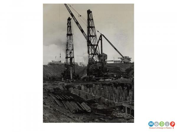Scanned image showing large cranes and pile drivers.