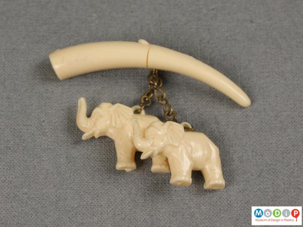 Front view of a brooch showing the hanging elephants.
