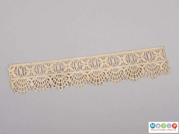 Top view of a parkesine lace edging sample showing the lace like pattern and the thread like texture.