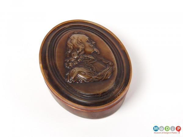 Top view of a snuff box showing the moulded portrait.
