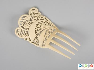 Top view of an imitation ivory comb showing the four teeth and the intricate design.