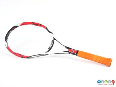 Side view of a tennis racket showing the oval shaped head and sraight handle.