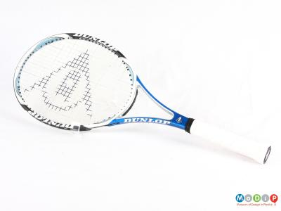 Side view of a tennis racket showing the oval head and straight handle.