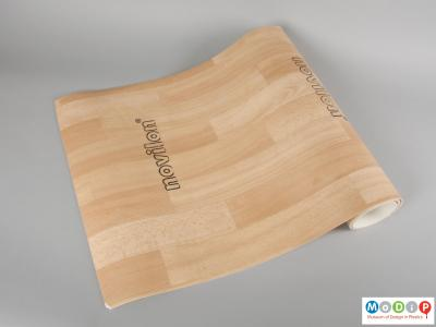 Side view of a sample of flooring material showing the printed wood block patterning.