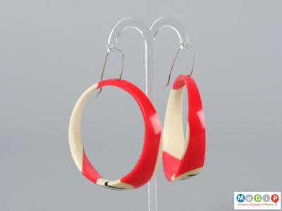 Side view of a pair of earrings made from pool balls hanging on an earring stand.