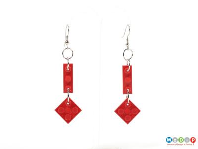 Front view of a pair of earrings made of Lego showing the two pieces used in each earring fixed together with metal loops.