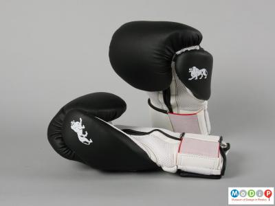 Side view of a pair of boxing gloves showing the black back section.