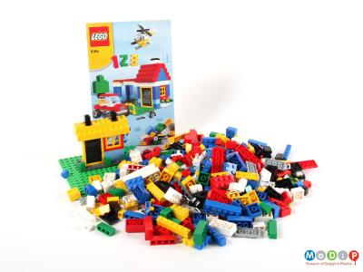 Side view of a Lego set showing all the bricks and the instruction booklet.