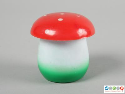 Side view of a set of tiddlywinks showing the toadstool shaped container.