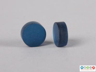 Side view of two blue contact lens buttons showing the thickness.