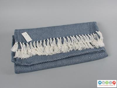 Side view of a blanket showing the edging tassels.