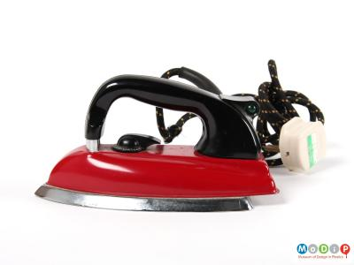 Side view of a Morphy Richards iron showing the red body and black curved handle.